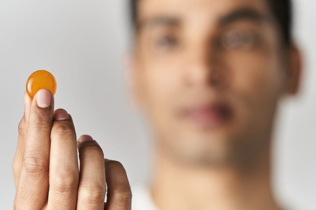 A man holds a sample of Healist Natural Calm Chews up to the camera.