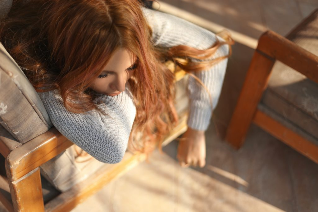 Photo: A white woman with red brown hair rests her head and arms on the arm of a chair, looking depressed or sick.