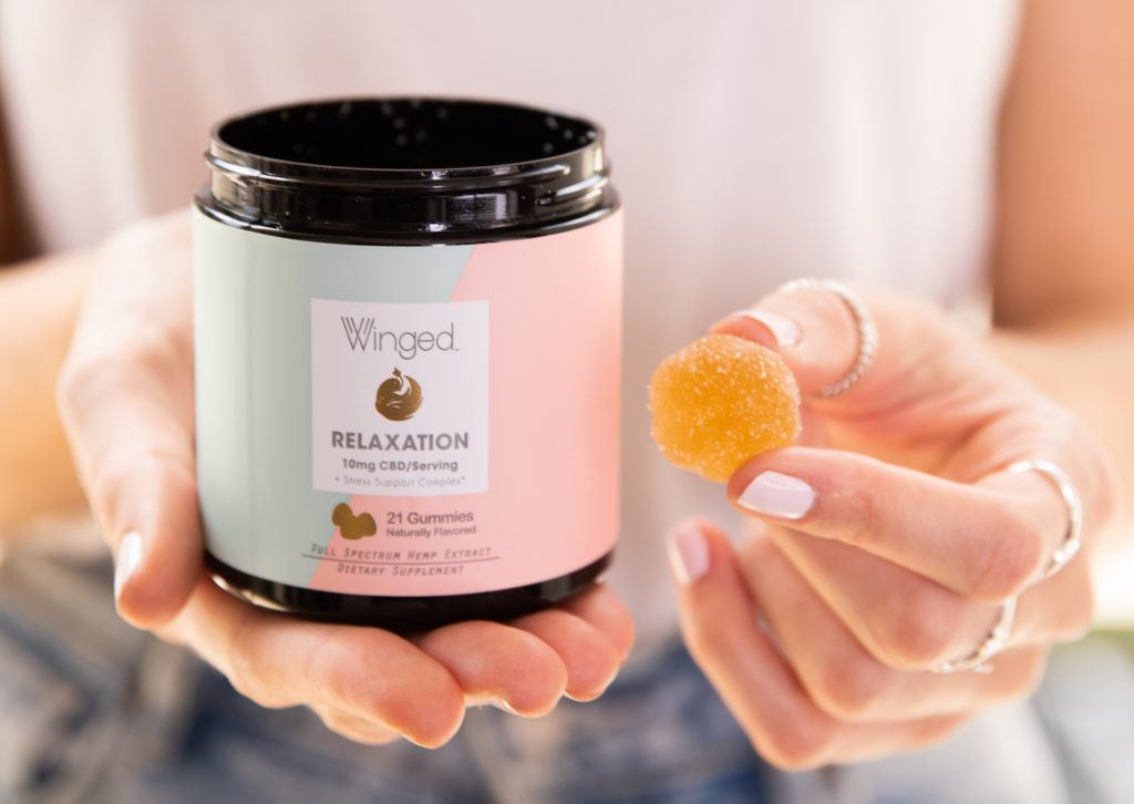 A woman holds an open jar of Wnged Relaxaton gummies in one hand, and a single gummy in the other.