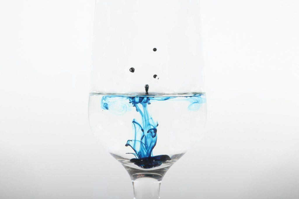 Photo: A glass of water with droplets of blue food coloring dropping into it, splashing on the surface and coilorfully mixing into the water.