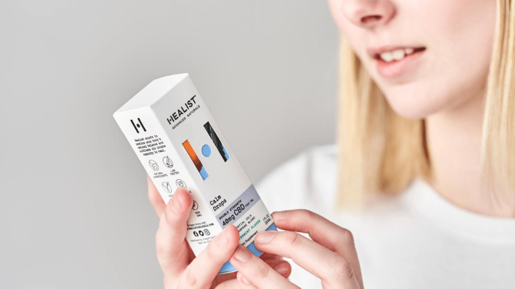 Phoyo: A smiling white woman with straight blonde hair examines a box of Healist Naturals Calm Drops.