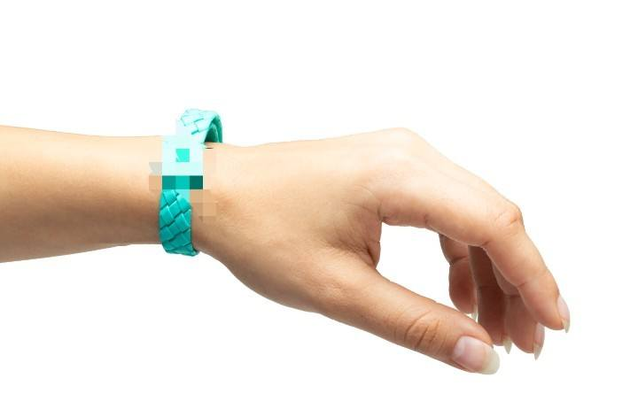 A CBD-infused plastic bracelet with the logo blurred.