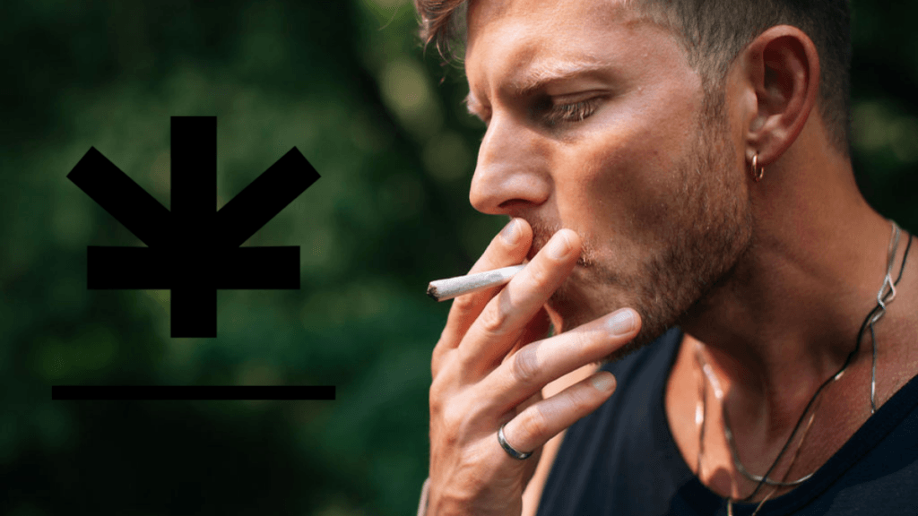 Photo: A white man with dirty blond hair and stubble, wearing a silver necklace and blue t-shirt, smokes a CBD pre-roll.