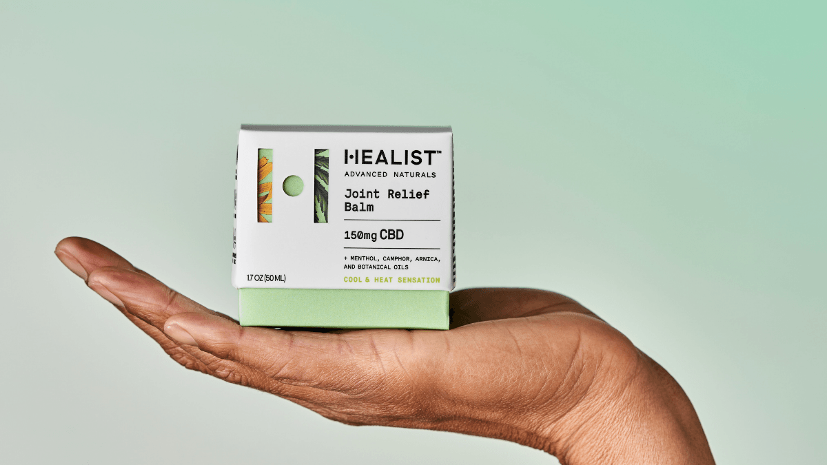 Photo: A person holds the Healist Naturals Joint Relief Balm box in their open palm.