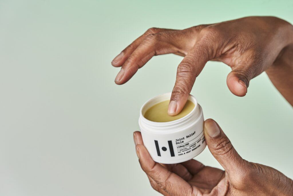 Someone holds the open bottle of Healist Naturals Joint Relief Balml in their hands as they gather some onto a finger for application to sore muscles.