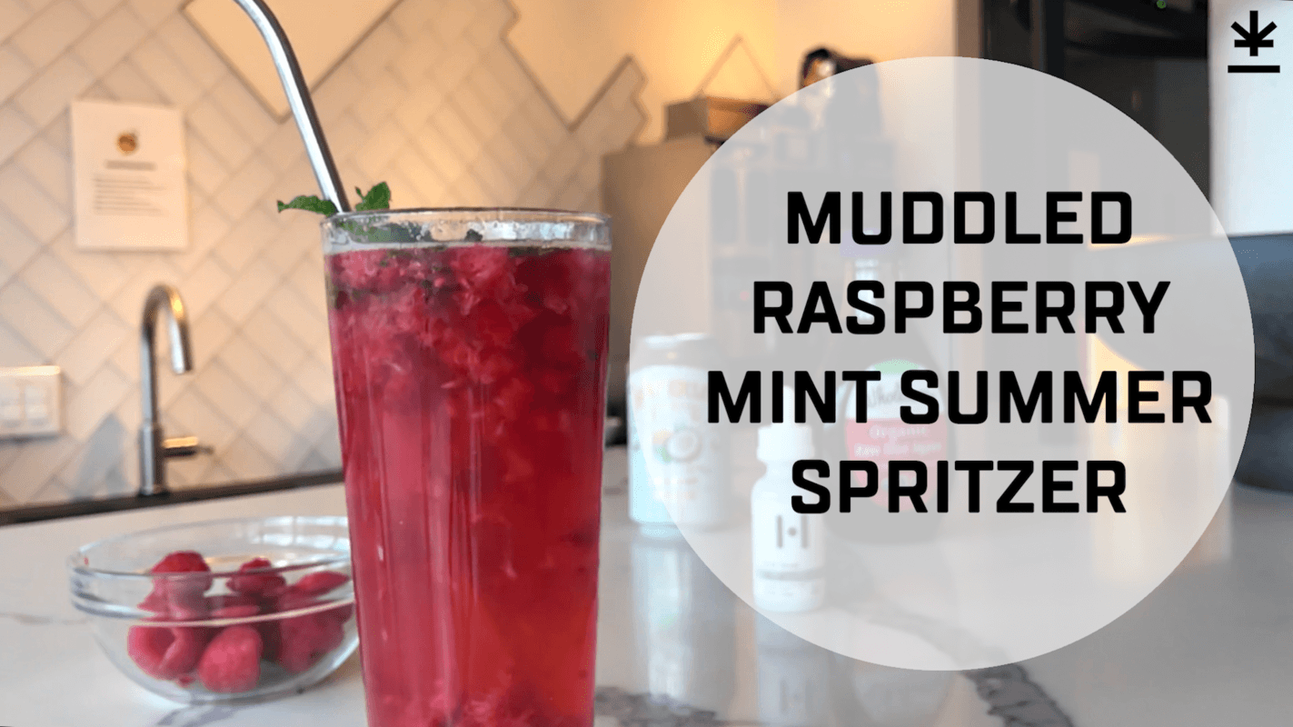A glass of raspberry CBD spritzer with a metal straw in it, garnished with a mint leaf. Text reads