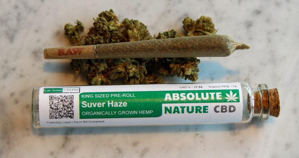 A CBD pre-roll posed with hemp flower, along with an Absolute Nature pre-roll
