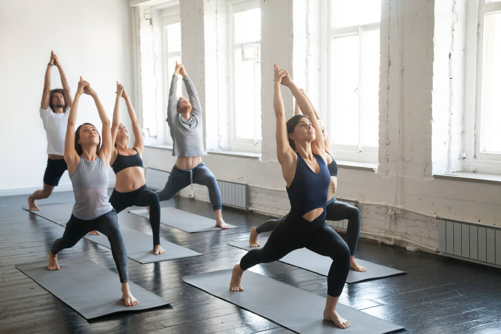 Group of young sporty attractive people practicing yoga lesson with instructor, standing together in Virabhadrasana 1 exercise, Warrior one pose, working out, indoor full length, studio background