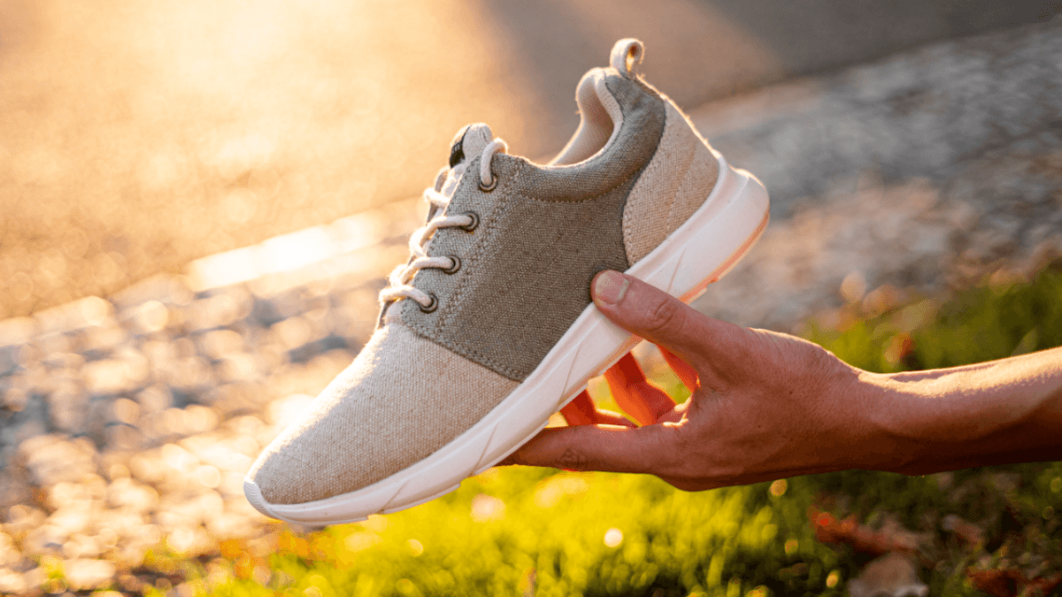 A hand holds up a single hemp sneaker in a natural gray with a white bioplastic sole. Hemp shoes could be an important part of a more sustainable future.