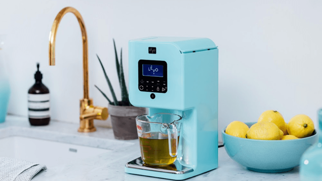 A blue Levo II Infusion Machine dispenses oil into a pyrex measuring cup. The appliance is sitting on a counter near a potted plant, a sink and a bowl of fresh lemons.
