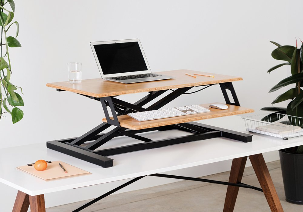 healthier home changes | desk riser on a table with laptop on it