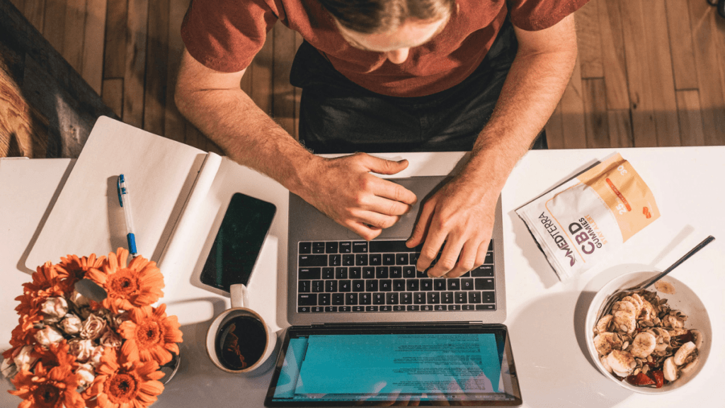 An overhead view of a desktop scene, with a white man working on a laptop in a t-shirt. Also on the desk is a cup of coffee, a notebook, a smartphone, some flowers, a bowl of granola with fruit, and Medterra Stay Alert CBD Gummies.
