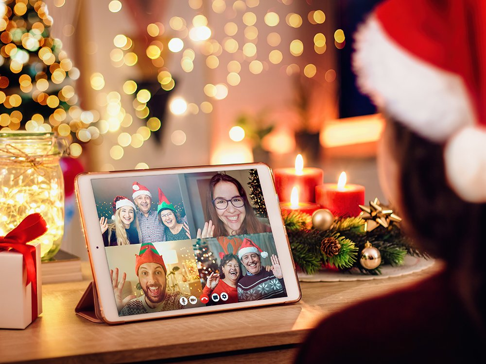 women on covid holiday celebrations   a woman in a santa hat taking a conference call on a tablet