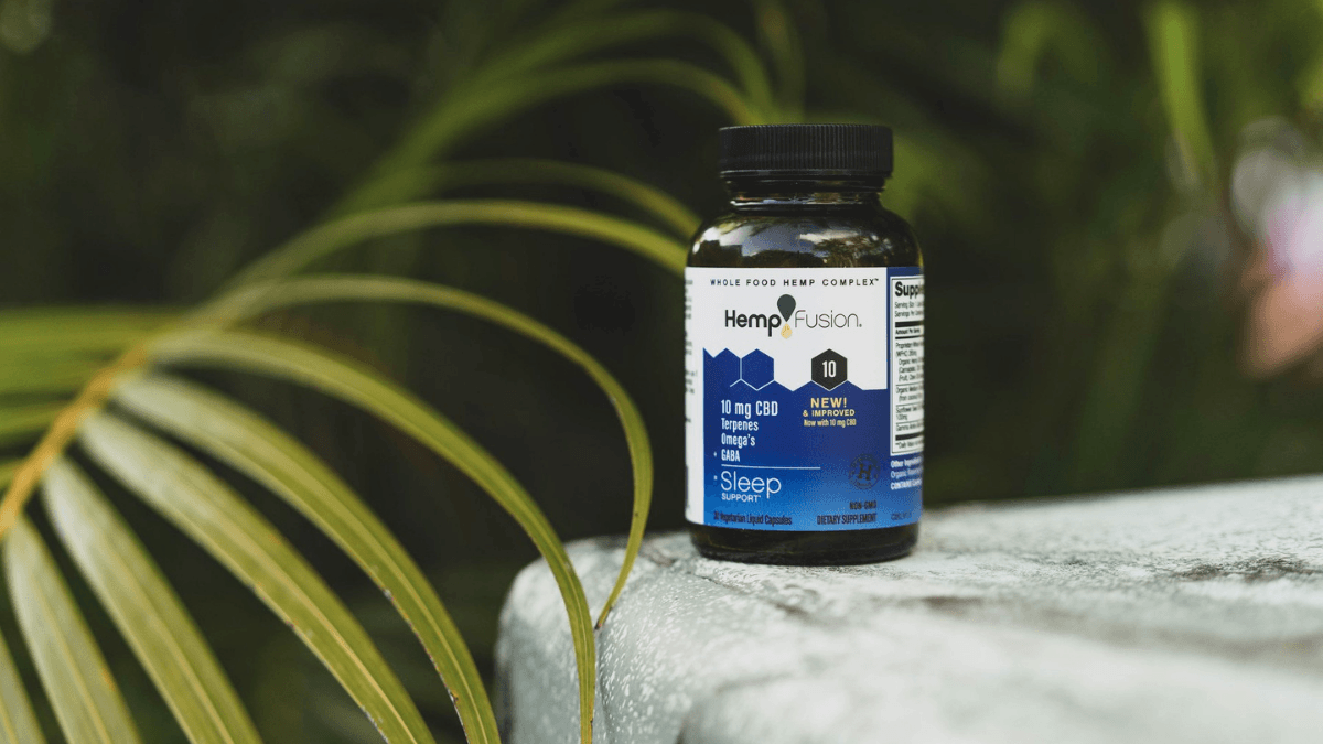 A bottle of HempFusion CBD Sleep Support capsules on a stone, surrounded by green tropical plants.
