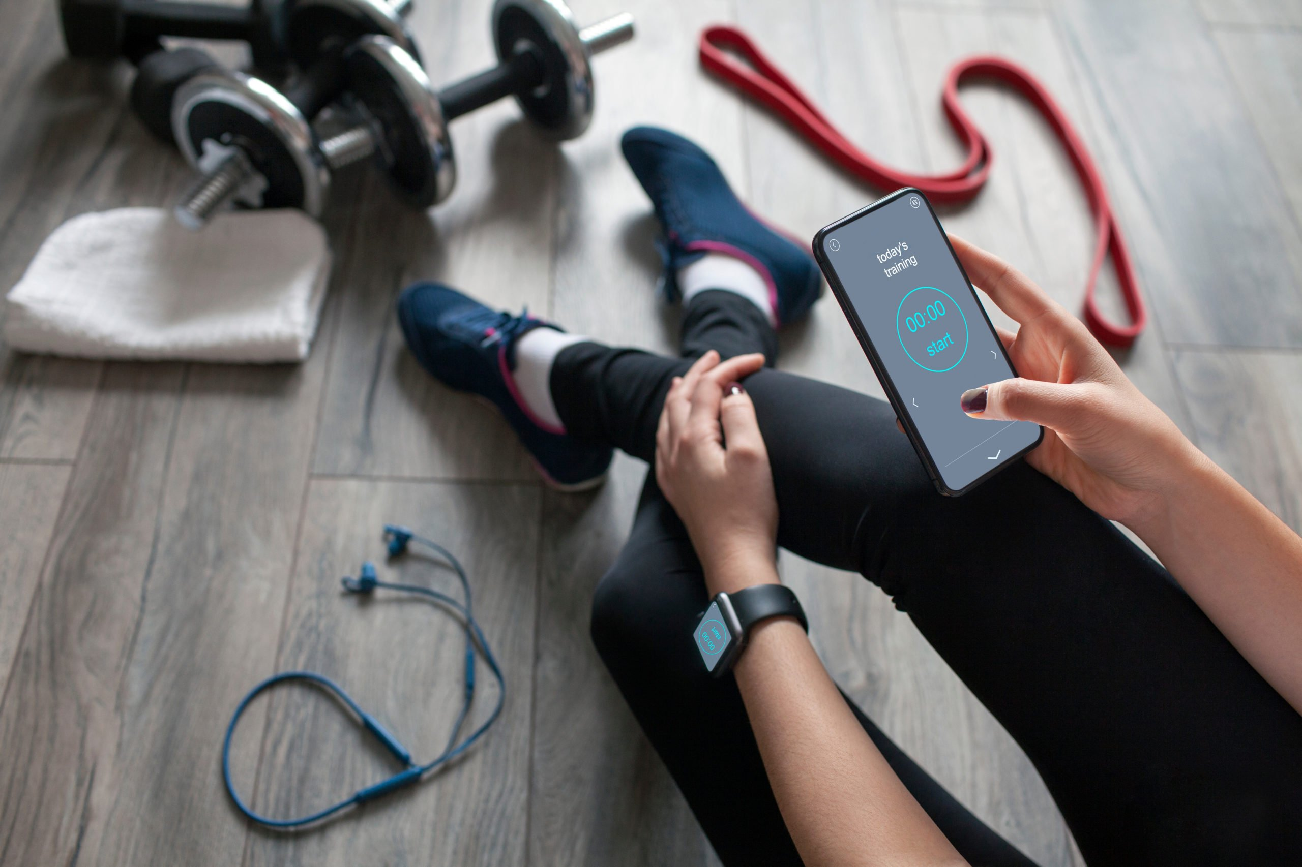 best fitness app | woman sitting and scrolling through their fitness app