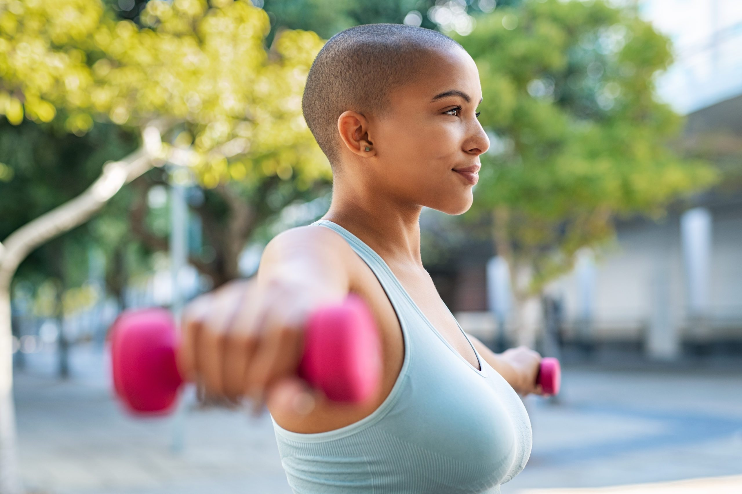 shoulder pain exercise | Active woman,using,dumbbells,in,the,park.,side,view