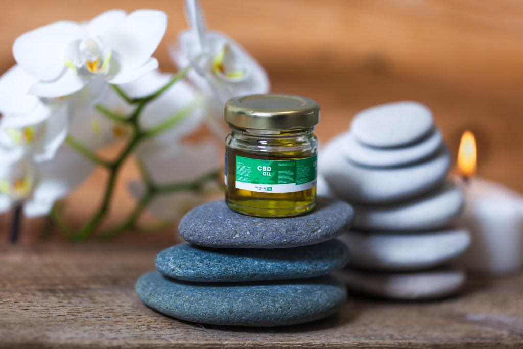 How long does it take for CBD oil to work? It depends on the method of ingestion. Photo: A generic bottle of CBD oil sits atop a stack of flat rocks with a candle and flowers in a meditative looking display.