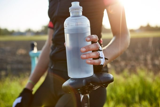cause dehydration | close up of cyclist holding water bottle