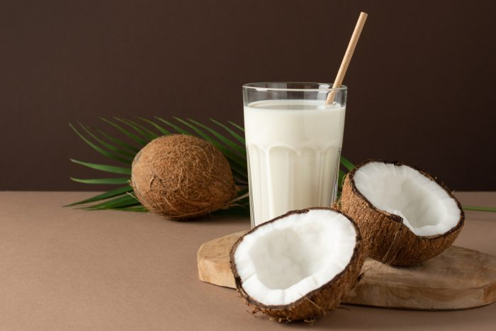 glass of coconut milk on brown background in studio setting