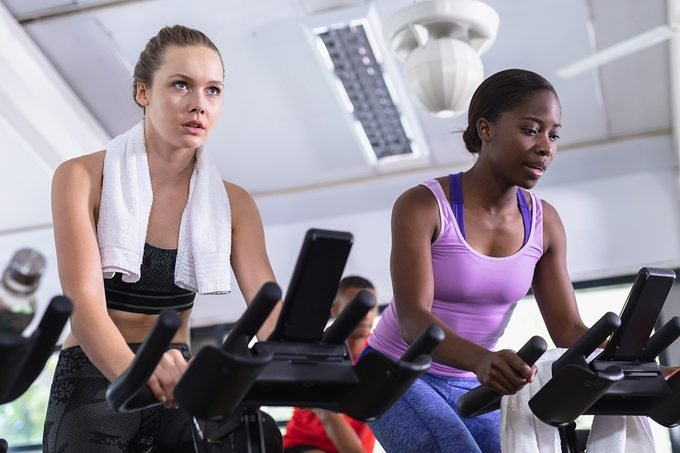 Front,view,of,diverse,fit,women,exercising,on,exercise,bike
